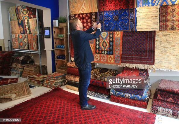 The Afghan Rug Shop owner James Wilthew photographs new arrivals on display to upload to the shop's social media accounts at his shop in Hebden...