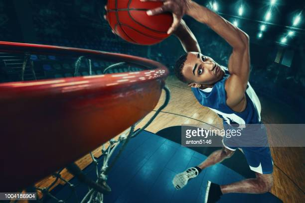 de afrikaanse mens basketballer springen met bal - basketbal teamsport stockfoto's en -beelden