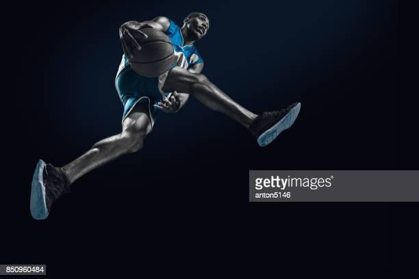 Le joueur de basket homme africain sautant avec ballon