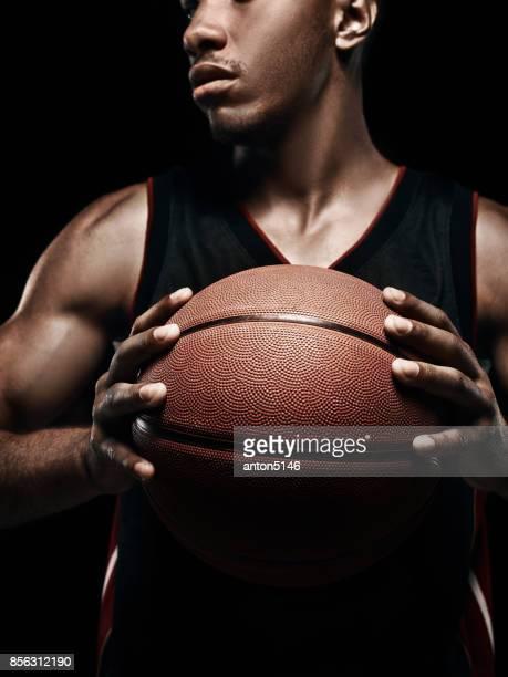 Der afrikanische Mann-Basketball-Spieler stehen mit ball