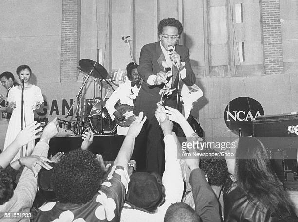 The African-American singer Al Green on a stage, greeting fans who are reaching up to him, 1981.