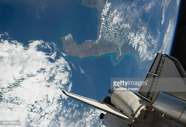 The aft part of space shuttle Endeavour backdropped against a part of Earth.