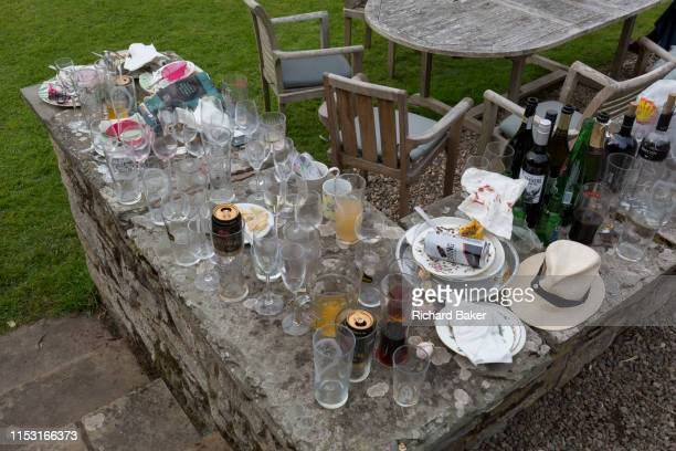 The aftermath debris of glasses bottles cans and plates the morning after a 50th birthday party spread around the garden in the Herefordshire...