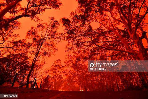TOPSHOT The afternoon sky glows red from bushfires in the area around the town of Nowra in the Australian state of New South Wales on December 31...