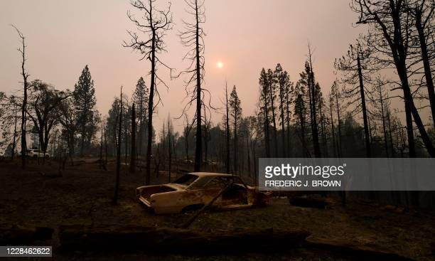 The afternoon sun is seen through a smoke-filled sky over fire-ravaged property in the Fresno County community of Pine Ridge in the foothills of the...
