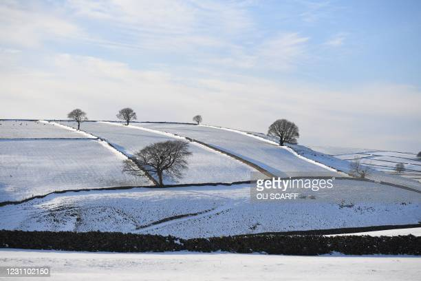 The afternoon sunshine lights up the snow-covered fields in the countryside near Tideswell in The Peak District in northern England on February 11 as...