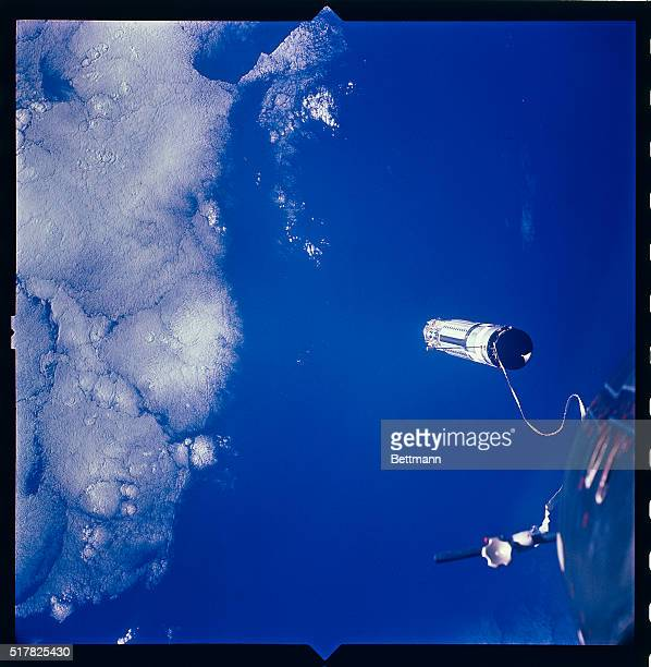 The Agena target vehicle is shown at a distance of about 100 feet from the Gemini 11 Spacecraft after a woven nylon tether was jettisoned The tether...