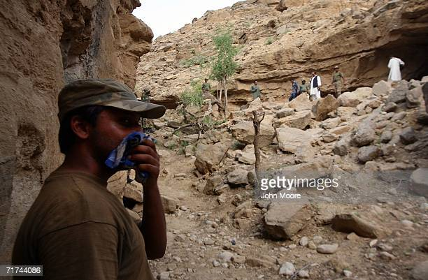 The air thick with the smell of death a Pakistani soldier stands near the destroyed entrance to a cave where the army says that the body of Baloch...