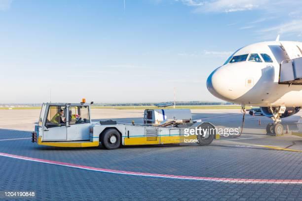 het vliegtuigsleepsysteem op de luchthaven - izusek stockfoto's en -beelden