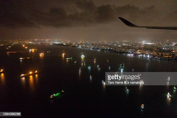 The airplane flying on many tankers on Singapore Strait in Singapore night time aerial view from airplane