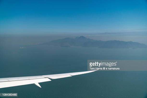 The airplane flying on South China Sea and Lantau Island in Hong Kong daytime aerial view from airplane
