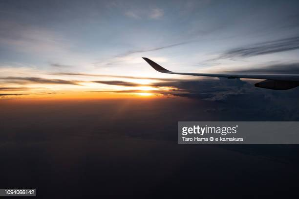 The airplane flying on sunset clouds on South Sumatra in Indonesia, sunset time aerial view from airplane