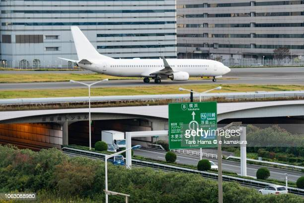 The airplane moving on Tokyo Haneda International Airport in Japan and Shuto Expressway Bayshore Route in Japan