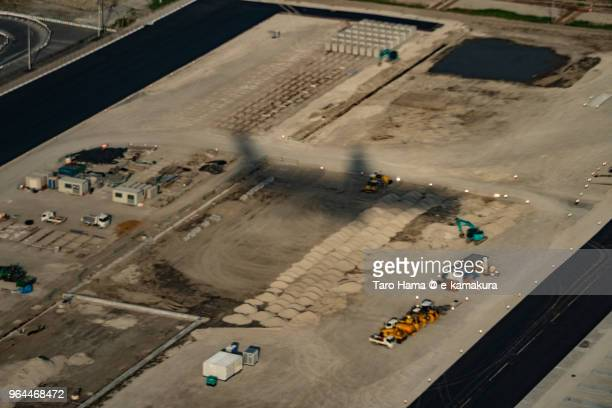 The airplane silhouette on reclaimed land in Tokyo Bay daytime aerial view from airplane