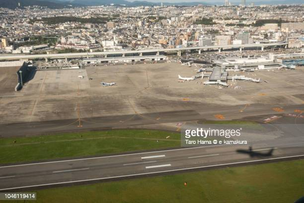 The airplane taking off Osaka International Airport Itami (ITM) in Japan daytime aerial view from airplane