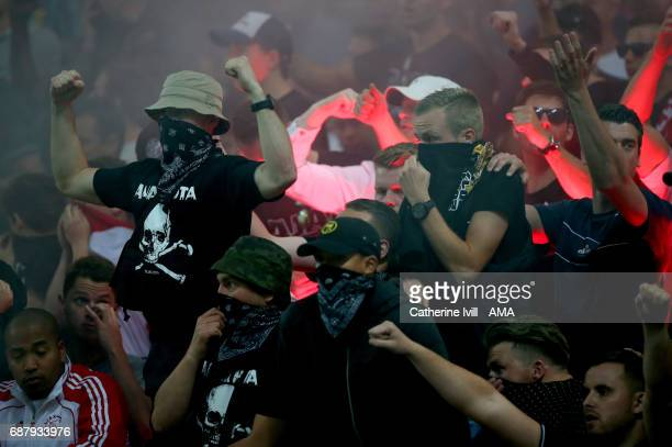 The Ajax Ultras fans with their faces covers as they let off flares during the UEFA Europa League Final match between Ajax and Manchester United at...