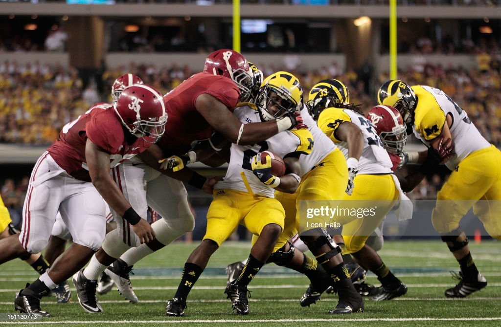 The Alabama defense swarms Denard Robinson #16 of Michigan during the third quarter of the game at Cowboys Stadium on September 1, 2012 in Arlington, Texas. Alabama defeated Michigan 41-14.