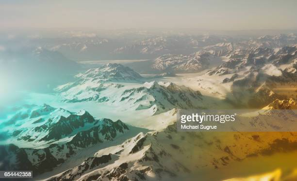 The Alaska Range of mountains is seen in abstract colors from the window of an airplane.