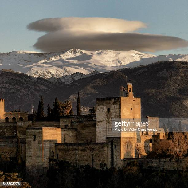The Alcazaba and snowed peaks of Sierra Nevada at sunset from the Albaicin, in Granada, Andalusia, SpainAlhambra illuminated and the Sierra Nevada mountain range at twilight from the Albaicin in Granada, Andalusia, Spain
