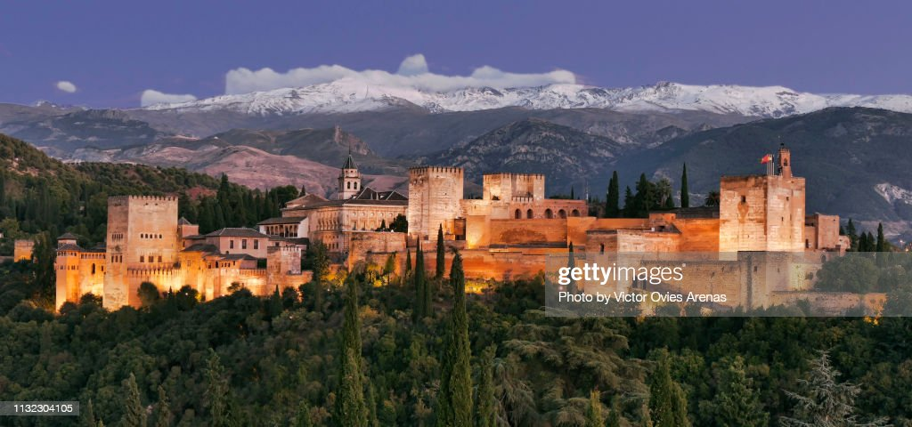 The Alhambra illuminated and the Sierra Nevada mountain range at twilight in Granada, Spain : Foto de stock