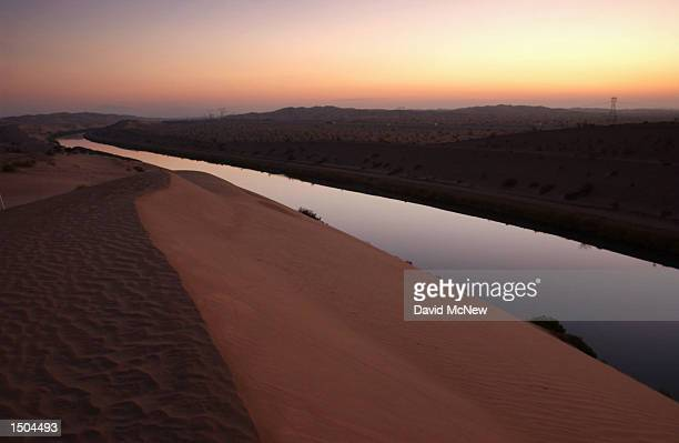 The All American Canal winds through the tall sand dunes of the American Sahara, also known as the Algodones Dunes or Imperial Dunes, as it carries...