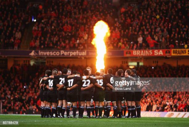 The All Blacks huddle on the pitch as pyrotechnics light the crowd prior to the start of the Invesco Perpetual rugby match between Wales and the New...