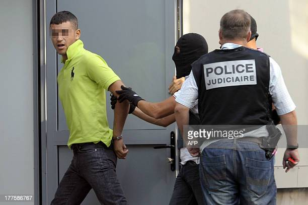 The alleged killer of 61 year old Jacques Blondel arrives escorted by police officers on August 24, 2013 at the Aix-en-Provence Law Court, in...