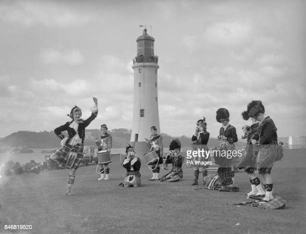 The AllGirl Scottish Highlanders of the State University of Iowa USA perform a dance on Plymouth Hoe in front of Smeaton Lighthouse The highlanders...