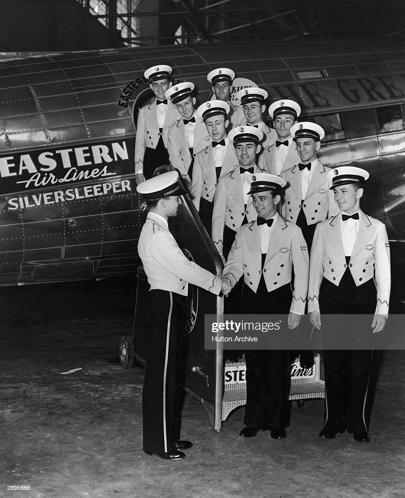 The all-male flight crew of an Eastern Airlines 'Silversleeper' airplane poses on the boarding stairwell of the plane, waiting to shake hands with a flight commander, circa 1935. They wear their airline uniforms.