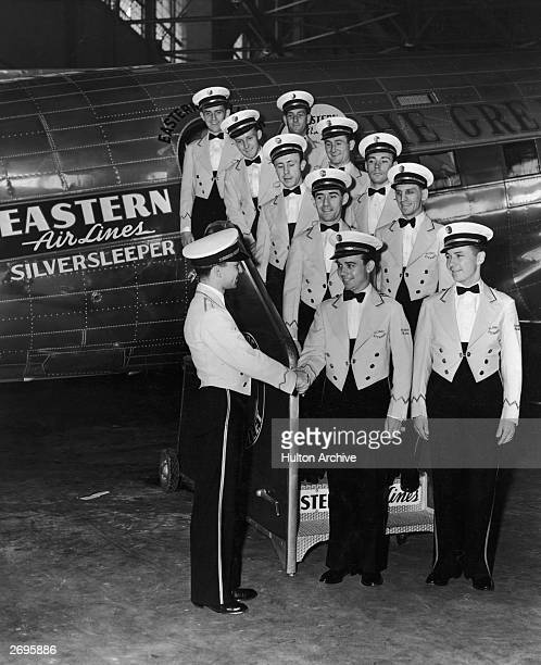 The allmale flight crew of an Eastern Airlines 'Silversleeper' airplane poses on the boarding stairwell of the plane waiting to shake hands with a...