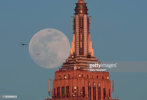 The almost full super snow moon rises at sunset behind the Empire State Building in New York City on February 18 2018 as seen from Hoboken New Jersey