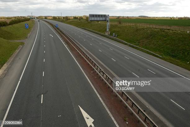 The almost-empty lanes of the M1 motorway are pictured near Pontefract, northern England on April 3 as vehicle traffic has been reduced and life in...