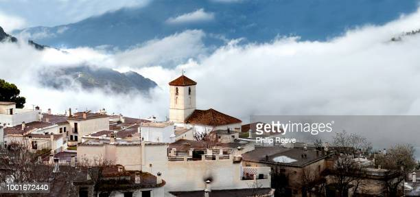 The Alpujarran village of Capileira and its Catholic church shrouded in mist, high up in the Sierra Nevada mountains in Spain's Andalucia region.