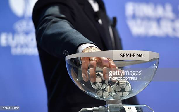 The ambassador for the UEFA Champions League final in Berlin KarlHeinz Riedle picks up a draw ball during the draw for the UEFA Champions League...