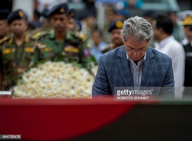 The ambassador of Italy to Bangladesh Mario Palma bows his head after placing a floral arrangement near caskets during a memorial service in Dhaka on...