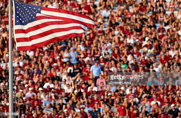 The America Flag blows in the wind as the crowd watches on during their game at WilliamsBrice Stadium on August 29 2013 in Columbia South Carolina