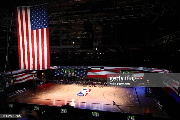 The America flag is seen as the Los Angeles Lakers and the LA Clippers wear Black Lives Matter shirt and kneel during the national anthem prior to...