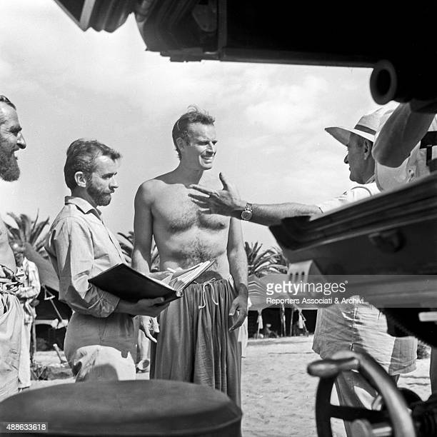The American actor Charlton Heston in a stage costume listening to the American director William Wyler on the movie set of Ben Hur With them some...