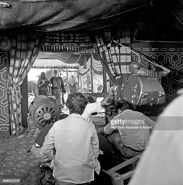 The American actor Charlton Heston playing in a tent on the set of the film Ben Hur A technician shoots the scene with a camera together with a boom...