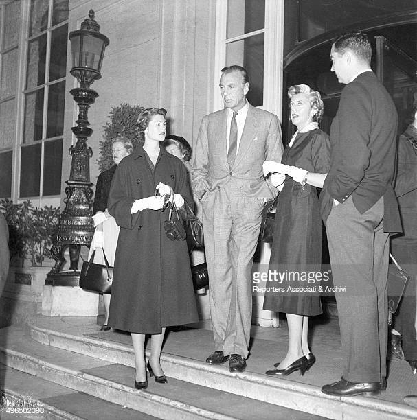 The American actor Gary Cooper with the American actress and wife Veronica Balfe and the daughter Maria Cooper waiting at the entrance of a building....