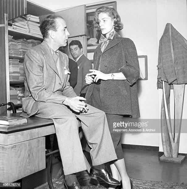 The American actor Humphrey Bogart sitting on a writing desk talking with the American actress Lauren Bacall at the Battistoni tailor's shop A man is...