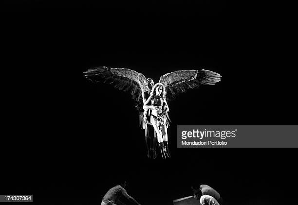 The American actor John Phillip Law in the guise of Pygar a winged angel flyes on the scenography above workers from the troupe holding in arms his...