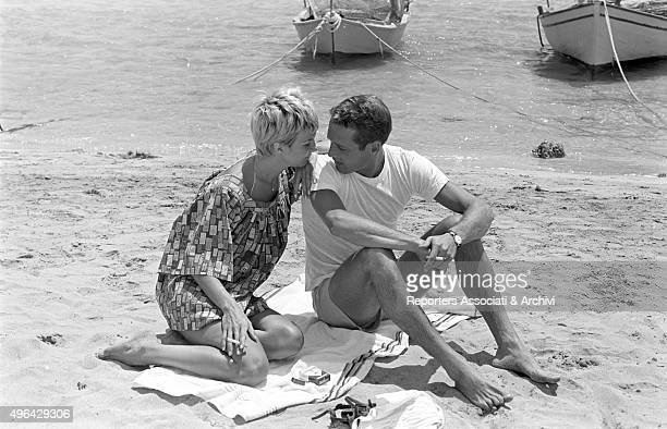 The American actor Paul Newman posing on a beach with the American actress producer and wife Joanne Woodward during a break in the shooting of the...