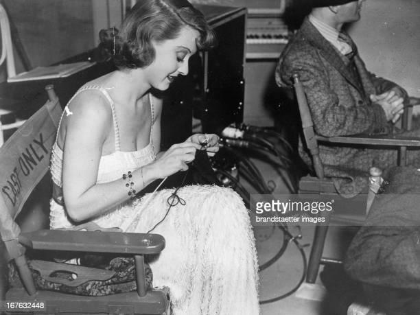 The american actress Bette Davis knits during a shooting break Photographie About 1937 Die amerikanische Schauspielerin Bette Davis strickt in den...