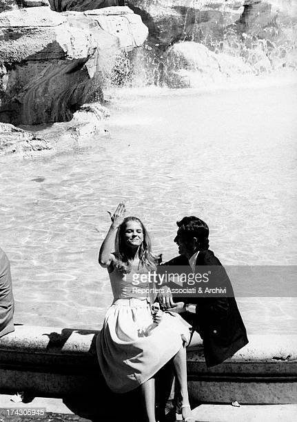 The American actress Candice Bergen and the Yugoslav actor Bekim Fehmiu seated at Trevi Fountain in the ritual act of throwing a coin into the water...