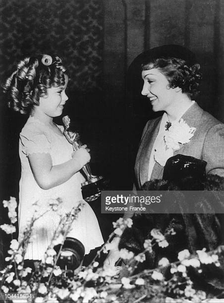 The American Actress Claudette Colbert Congratulating Shirley Temple Who Had Just Become An Oscar In Hollywood In 1935.