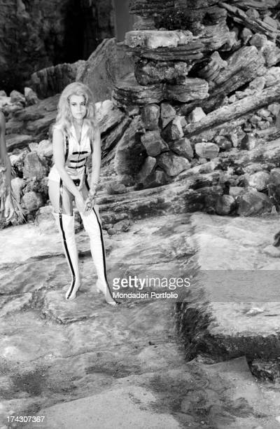 The American actress Jane Fonda adjusts her boot on a rocky scenery during a break from the filming of Barbarella she play the leading role of a...