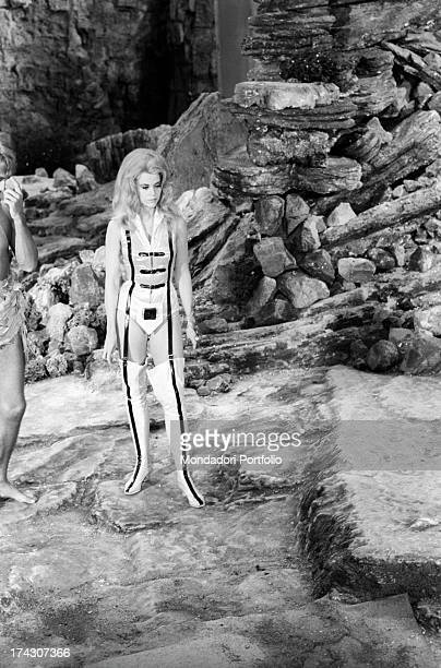 The American actress Jane Fonda stands on a rocky scenery looking around during a break from the filming of Barbarella she wears the clinging space...