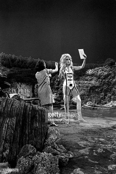 The American actress Jane Fonda wearing a clinging space suit is assisted by the make up operator during a pause from the filming of Barbarella...