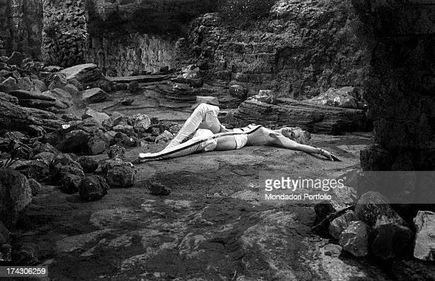 The American actress Jane Fonda wearing a clinging space suit is lying on the ground of a rocky scenography she's playing the role of astronaut...
